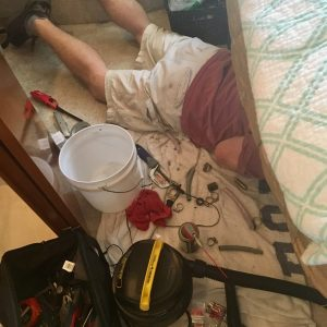 Man lying on floor doing a repair