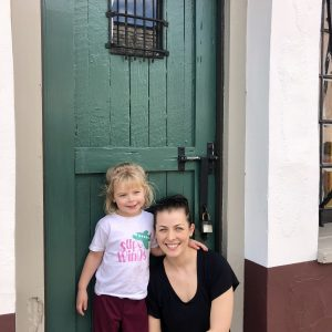 girl and her mother in front of green door
