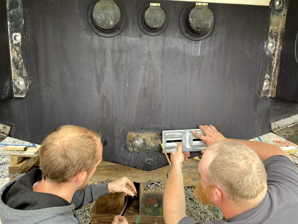 two men putting a zinc on the stern of a boat