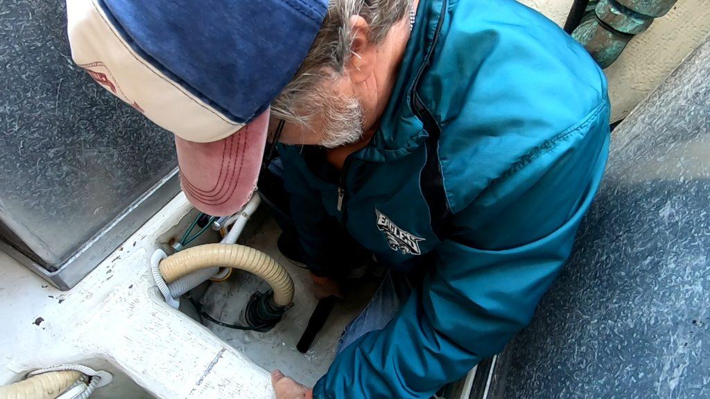 man vacuuming water from boat bilge