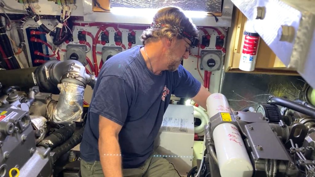 man in boat engine compartment